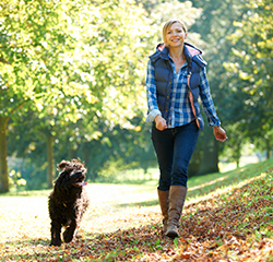 A woman walks her dog in the autumn