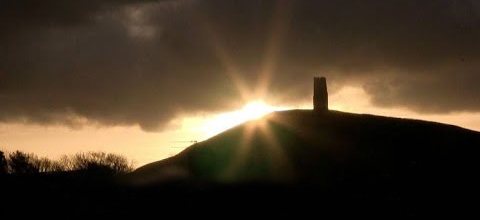 Solstice sun rolling up Glastonbury Tor