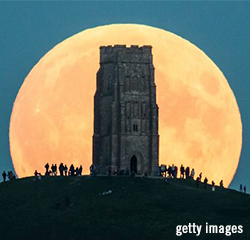 Full Lunar Super Blood Moon Eclipse rises behind Glastonbury Tor