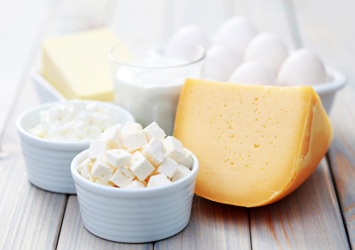 An image of a group of products; eggs, butter and cheese slabs and cubes of cheese in a bowl