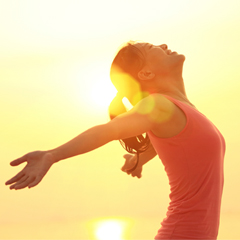 Woman stretching her arms out in the sunshine