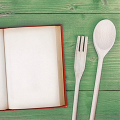 Open recipe book with kitchen cutlery